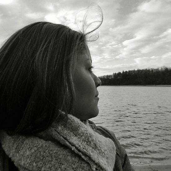 Side view of woman by lake against sky