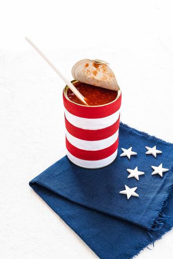 white and red striped tin filled with tomato sauce and white stars on blue cloth in american style 4th Of July American Flag July Patriotic Patriotism Red Stripes Tomato Soup USA United States Of America USA America American Colors Blue Cloth Food Fourth Homeland Independence Day Independence Day Celebration Star Stars And Stripes States Symbol Tin White