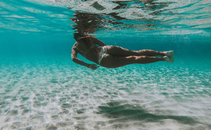 Rear view full length of woman swimming in sea