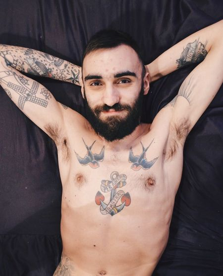 Portrait Of Smiling Shirtless Man With Hands Behind Head Lying On Bed