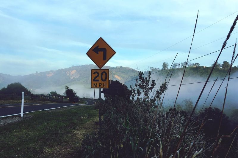 Fog Foggy Sky Tree Tranquility Tranquil Scene Nature Road Sign Communication Outdoors Mountain No People Day Beauty In Nature Scenics Cloud - Sky Landscape Grass Electricity Pylon Turn Ahead Change Coming Future mdscape] fu Twenty Curve
