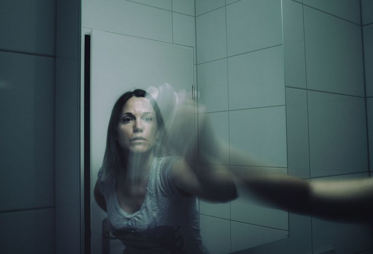 Blurred motion of woman cleaning mirror