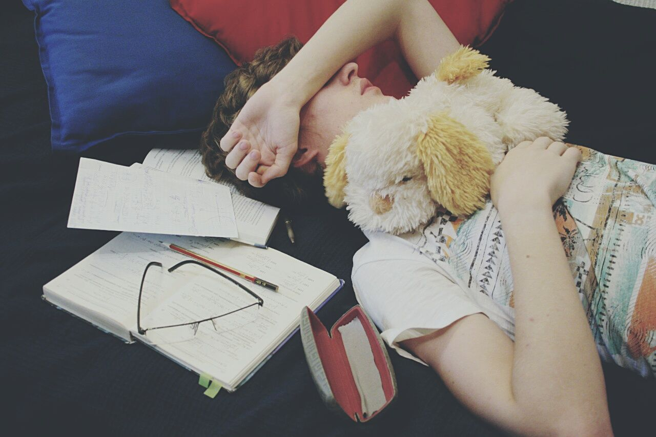Teenage boy sleeping by books and stuffed toy on bed at home