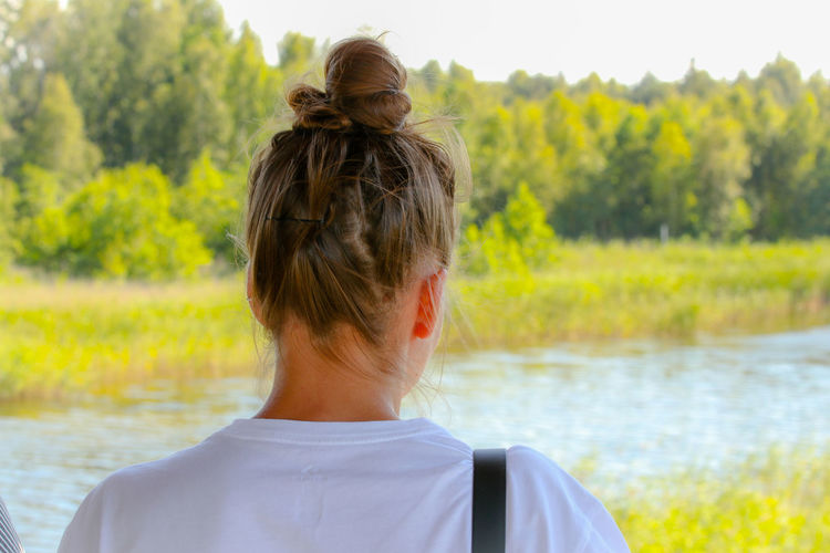 Rear view of woman looking at lake against trees