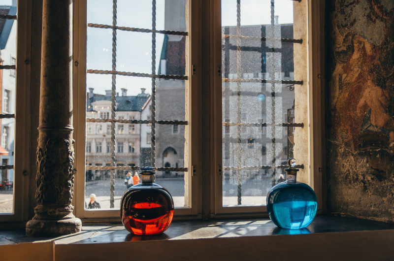 View of the Town Hall Square from the Raeapteek Pharmacy. Red and blue bottles in the oldest pharmacy in Europe. Bottle Bottles Estonia Europe Farm Glass - Material Indoors  Indoors  Interior Design Landmark Old Town Oldest Pharmacy Red And Blue Tallinn Tourism Tourist Tourist Attraction  Tourist Destination Transparent Window Window Sill Beutiful Organized