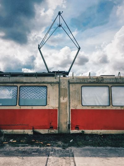 Abandoned tram against cloudy sky