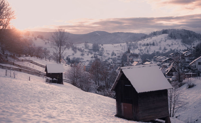 Wooden barns and cabind on snow covered field by buildings against mountains and sky