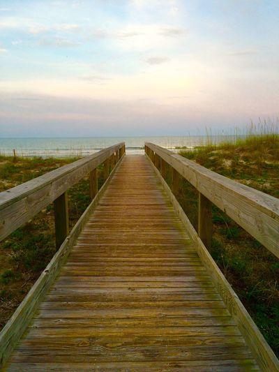 Boardwalk on beach against sky during sunset