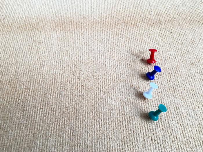 High angle view of colorful thumbtacks on burlap