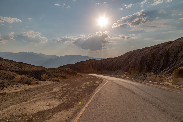 A road with a scenic view, in Death Valley National Park, California Death Valley Death Valley National Park Arid Climate Beauty In Nature Climate Cloud - Sky Desert Diminishing Perspective Direction Environment Landscape Mountain Range Nature No People Non-urban Scene Outdoors Road Scenics - Nature Sky Sun Sunlight The Way Forward Tranquil Scene Tranquility Transportation