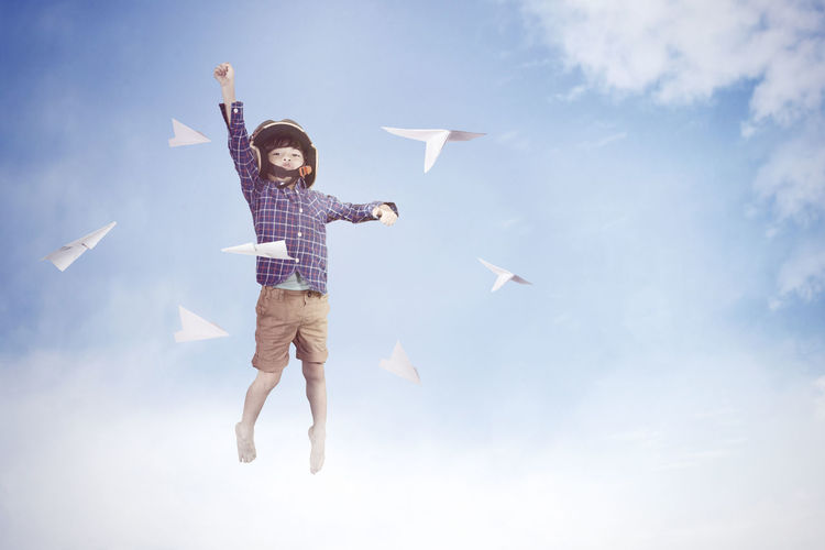 Low angle view of boy flying against sky