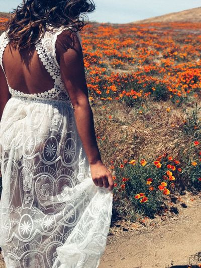 Rear view of woman in white dress standing by flowering field