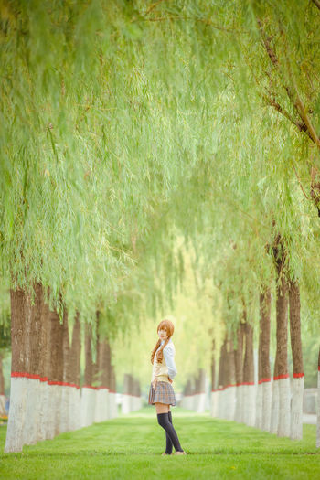 Side view of young woman standing on grass against trees