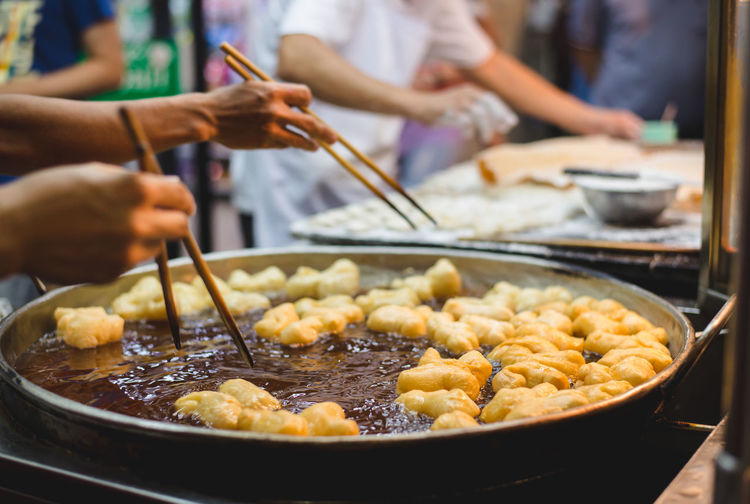 Food Food And Drink Preparation  Focus On Foreground Kitchen Utensil Holding Human Hand Freshness Real People Market Hand Midsection Incidental People Market Stall Indoors  Household Equipment Meat Preparing Food Selective Focus Occupation Street Food Chinese Donut Chinese Bread Stick China Town Chinatown Powdered Sugar
