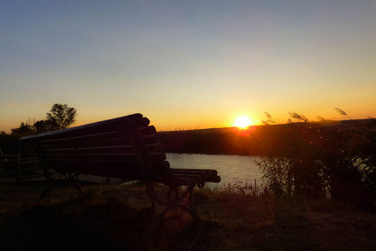 Bench on shore against sky during sunset