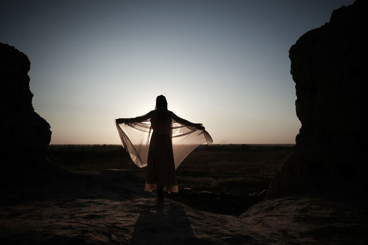 Rear view of silhouette woman wearing traditional clothing standing on rock