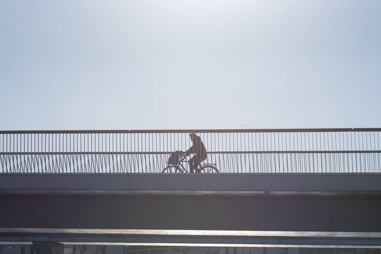 Low angle vie of man riding bicycle on bridge against clear sky during sunny day