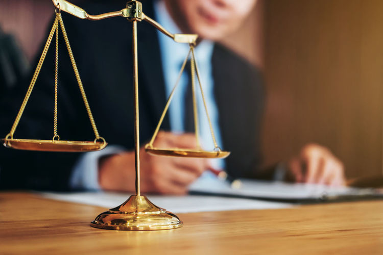 Midsection Of Lawyer Working By Weight Scale On Table