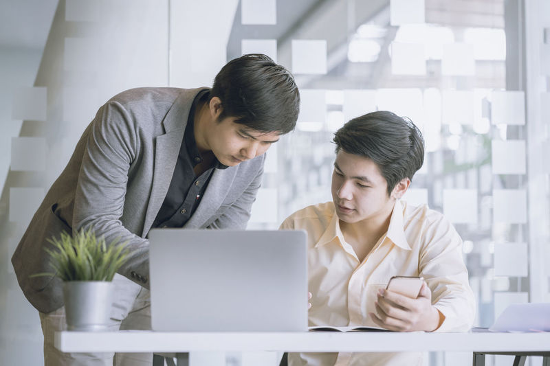 Male colleagues discussing at desk in office