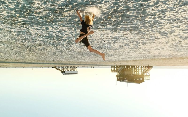Upside Down Image Of Boy Jumping On Sand At Beach