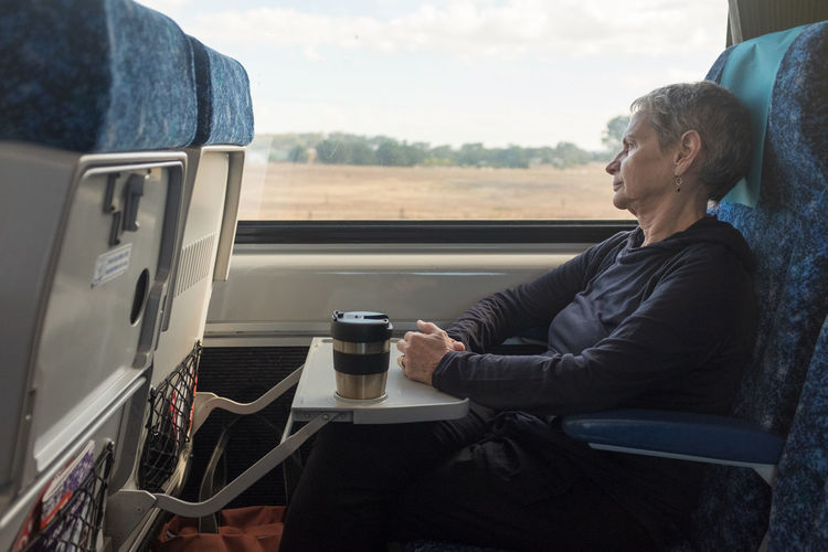 Senior woman on train Sitting Real People Window Lifestyles One Person Drink Casual Clothing Cup Leisure Activity Looking Mug Mode Of Transportation Food And Drink Coffee Transportation Indoors  Contemplation Senior Women Train - Vehicle Women