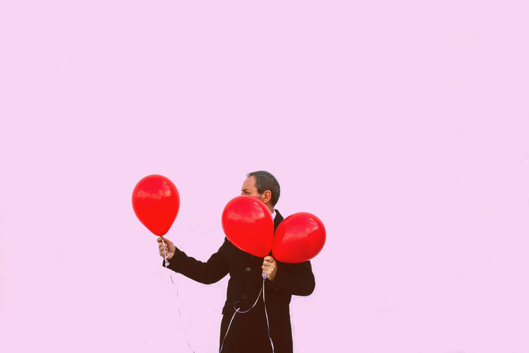 Man with balloons standing against pink background