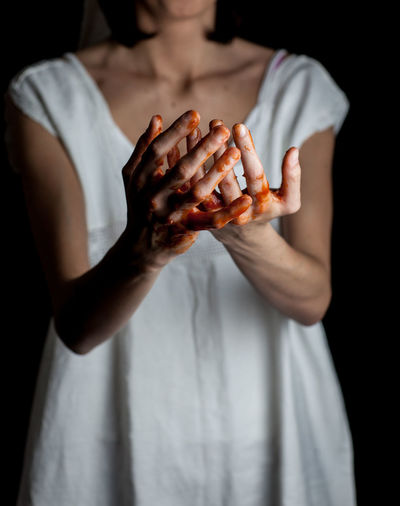 Midsection Of Woman With Blood Hands Against Black Background
