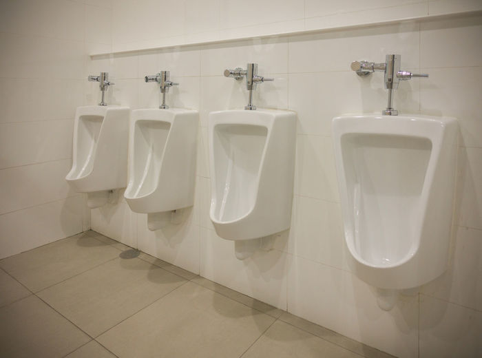 Urinals by wall in bathroom