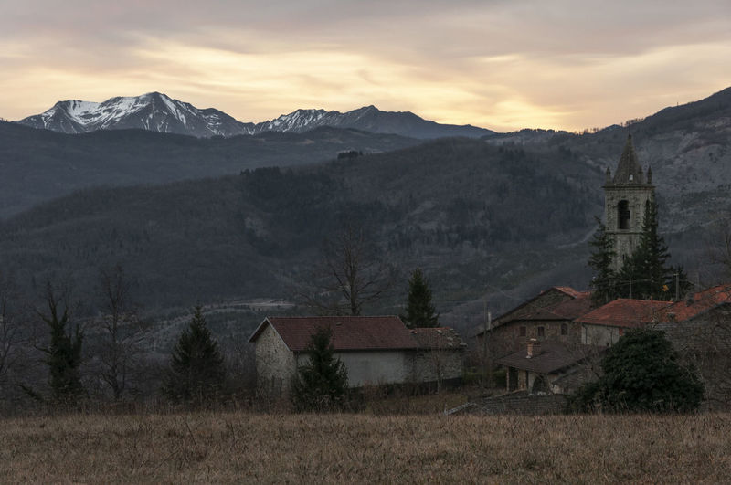 Houses by mountains against sky during sunset