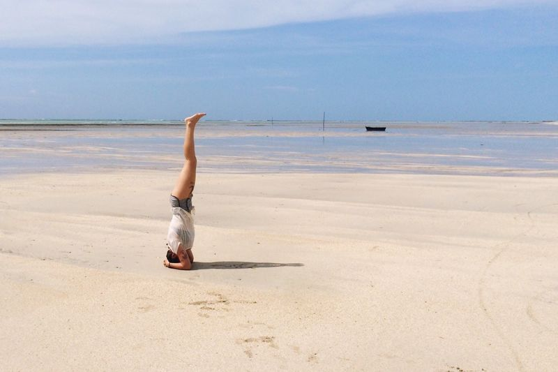 Woman performing headstand at beach