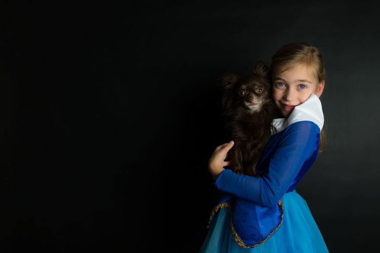 portrait of a girl in a bleu dress holding a chihuahua in her arms. in front of a black background Girl Dress Childrenphotography Dog Chihuahua Dressed Up Adorable Child Childhood Children Only Portrait Black Background People Looking At Camera One Person Studio Shot Indoors