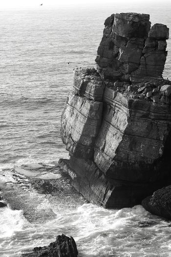 This rock was formerly hung up on the mountain and formed a beautiful natural bridge. It remains majestic. Kevincaetano Rock Formation Rock - Object Rock Mountain Blackandwhite Black And White Travel Destinations Sea Beach Water One Person Leisure Activity Nature Sand Outdoors Wave Horizon Over Water Lifestyles Full Length Vacations