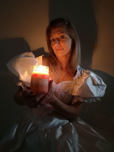 Portrait of woman holding lit candle