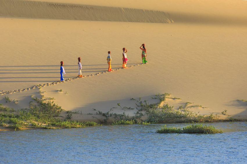 Ninh Thuan province, Vietnam - November 26, 2016 : the ethnic Cham women collecting water in the small lake in the middle of the sand dunes, they had to overcome dunes with water jars on their heads. This is their daily work Hill Traditional Agriculture Asian  Backgrounds Beautiful Carry Cham Colorful Culture Desert Dress Dunes Footmark Footprints Lifestyle Ripples Sand Shadow Sunlight Tourism Travel Vietnamese Walk Work