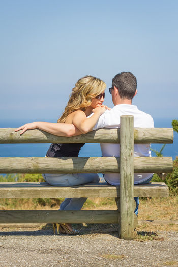 Couple sitting against clear sky