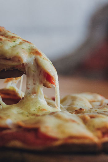 Hot Pizza Slice with Melting Cheese on a rustic wooden table Dinner Food And Drink Homemade Hot Lunch Meal Melting Rustic SLICE Snack Cheese Close-up Day Delicious Dripping Food Food And Drink Freshness Healthy Eating Indoors  Italian No People Pizza Pull Tomato