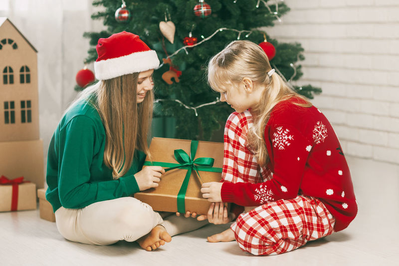 Two happy and cheerful sisters in fashionable new year's outfits open gifts at home