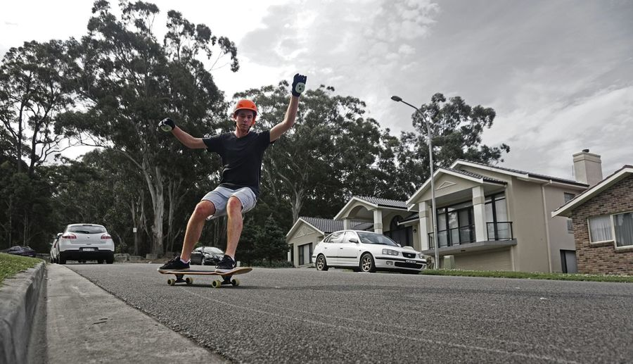 Man Skateboarding On Road Against Sky