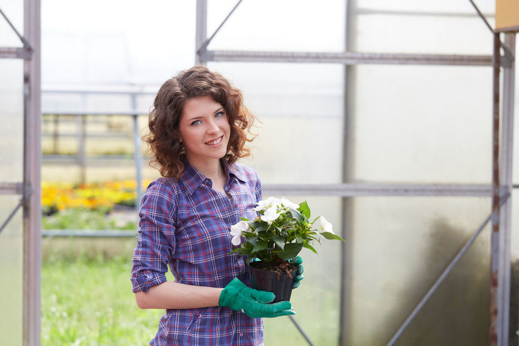 Portrait of woman holding plant in greenhouse
