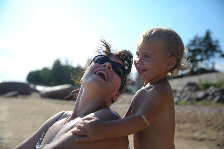 Happy Woman And Boy On Beach Against Sky