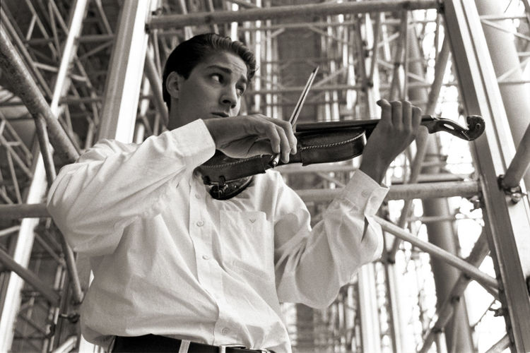 Low angle view of man playing violin while standing by built structure