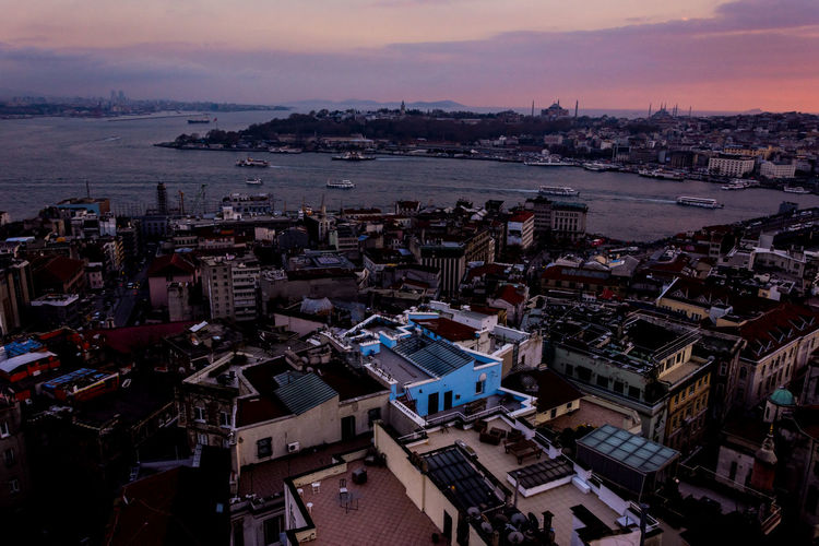 High angle view of city at seaside during sunset