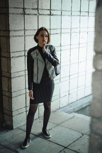 Portrait Of Young Woman Wearing Jacket While Standing Against Patterned Wall