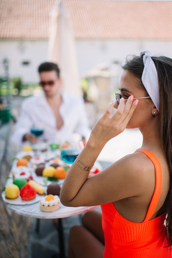 Midsection of woman holding sunglasses while sitting outdoors
