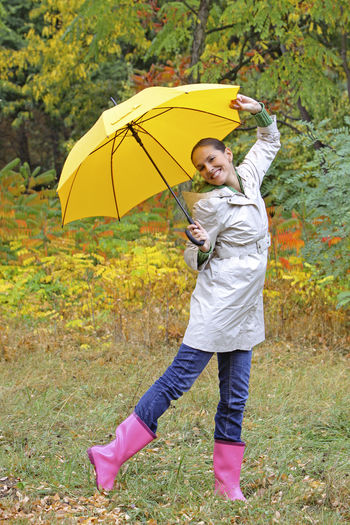Woman with umbrella in the autumn Umbrella Autumn Rainy Day Woman Happy Funny Protection Full Length One Person Security Rain Wet Yellow Standing Happiness Smiling Nature Front View Day Child Leisure Activity Boot Rubber Boot Outdoors
