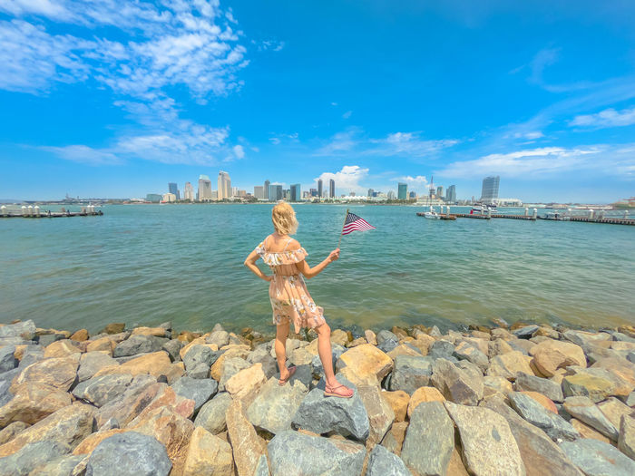 Tourism and travel in California, West Coast, USA. Blonde lady looking San Diego skyline with American flag waving from Coronado Island. Tourist woman in summer holidays. Cityscape in San Diego Bay. United States America American American Flag Woman People Female Girl California San Diego San Diego, California Beach Sea Seascape Skyline Cityscape Shore Nature Vacations Holiday Summer Lifestyles Tourist Coronado Coronado Beach Coronado Island Water Sky One Person Rock Cloud - Sky Real People Leisure Activity Rock - Object Day Full Length Standing Human Arm Solid Beauty In Nature Rear View Limb Arms Outstretched Arms Raised Outdoors
