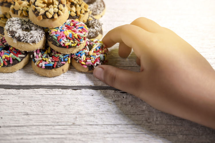 Close-up of hand holding ice cream on table