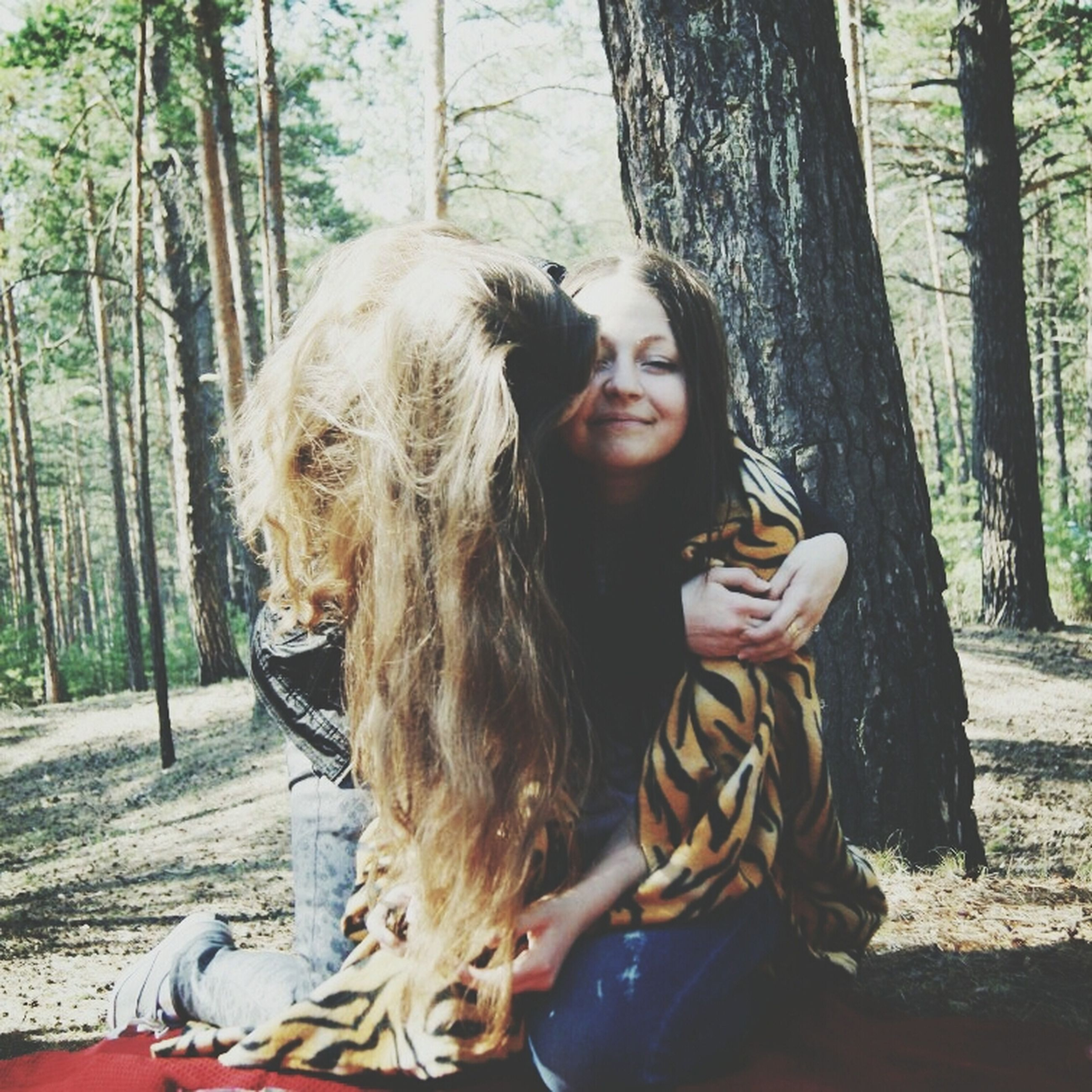 young adult, long hair, young women, person, tree, lifestyles, looking at camera, casual clothing, portrait, leisure activity, front view, smiling, tree trunk, brown hair, blond hair, day, outdoors