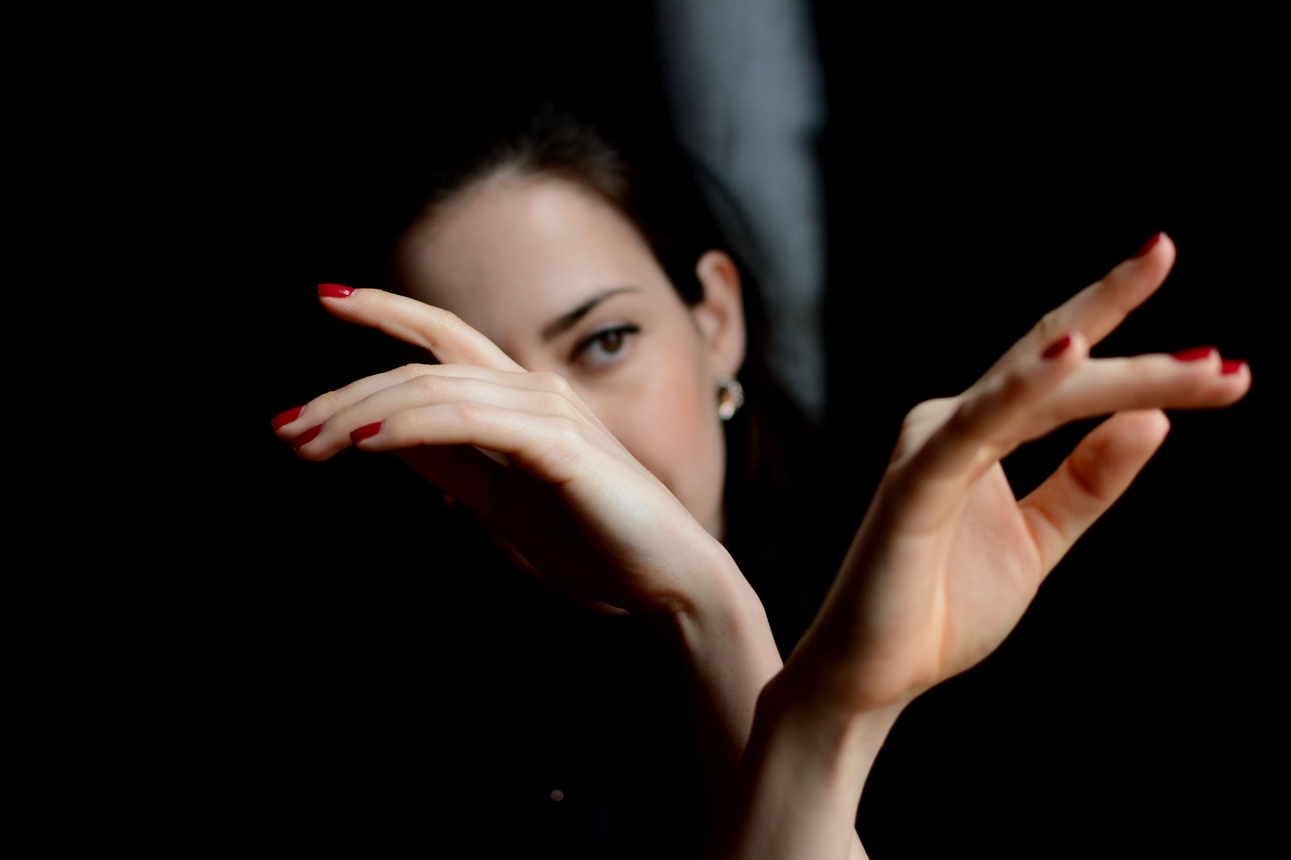 black background, studio shot, person, indoors, lifestyles, close-up, human finger, animal themes, part of, holding, one animal, copy space, side view, leisure activity, touching, cropped