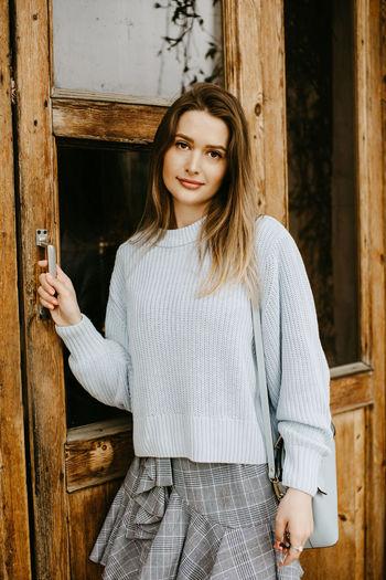 Portrait of woman standing by door